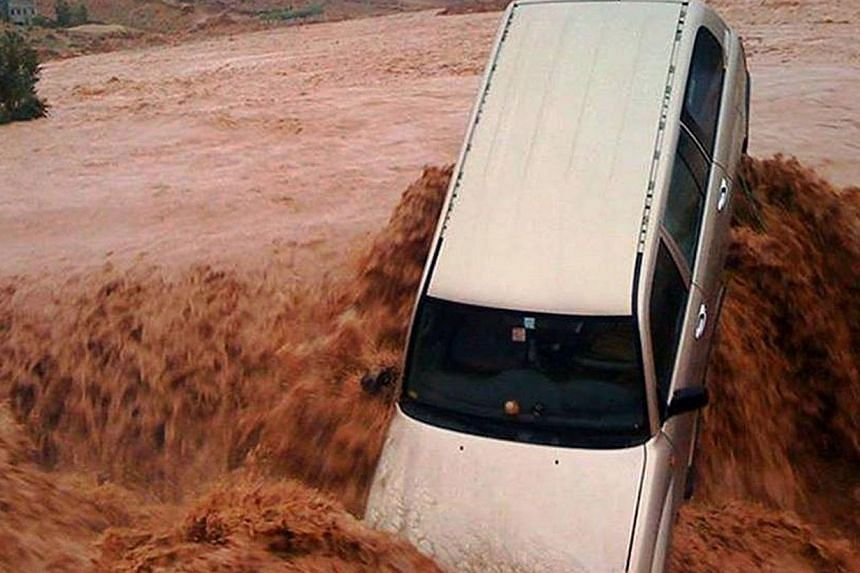A car is carried away by flood waters Nov 23, 2014 in the southern region of Ouarzazate in Morocco. -- PHOTO: AFP