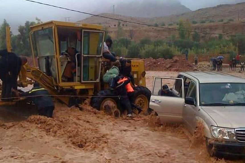 Firemen rescue a driver trapped in flood waters Nov 23, 2014 in the southern region of Ouarzazate in Morocco. -- PHOTO: AFP