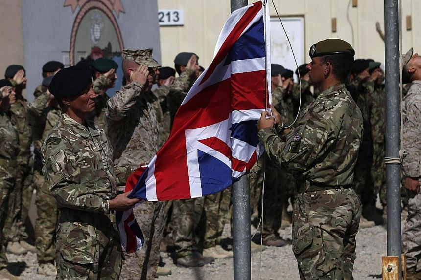 British troops lower the Union Flag during a ceremony marking the end of operations for US Marines and British combat troops in Helmand on Oct 26, 2014. Britain withdrew its last military forces from southern Afghanistan on Monday after 13 years