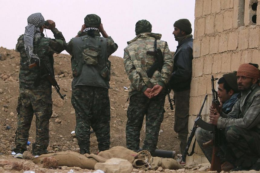 Kurdish People's Protection Units (YPG) use binoculars to keep watch in southern Ras Al-Ain countryside, during clashes with Islamic State in Iraq and Syria (ISIS) fighters in the area on Nov 21, 2014.At least two Britons are among around 15 We