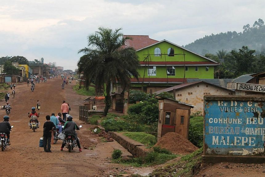 People walking and riding motorcycles in a street of the town of Beni, in the north east of the Democratic Republic of Congo, on Oct 20, 2014.About 100 people were slaughtered last week in the east of the Democratic Republic of Congo near Beni
