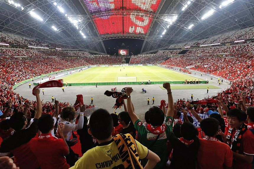 Fans cheering as Singapore scores an equaliser against Thailand in the AFF Suzuki Cup match at the new National Stadium last night.