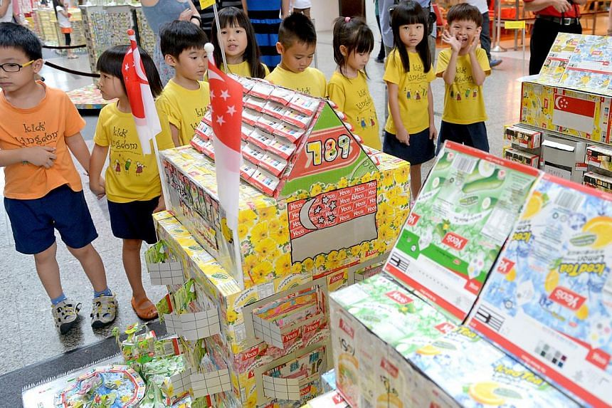 Kindergarten children looking at housing structures made of recycled material. A scheme has been launched to encourage pre-schoolers to help protect the environment.-- PHOTO: ST FILE