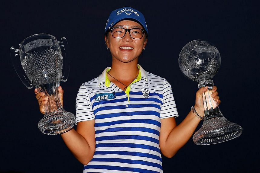 Lydia Ko of New Zealand poses with the CME Tour Championship trophy and the CME Race for the Globe trophy following the final round of the CME Group Tour Championship at Tiburon Golf Club in Naples, Florida on Nov 23, 2014. -- PHOTO: AFP