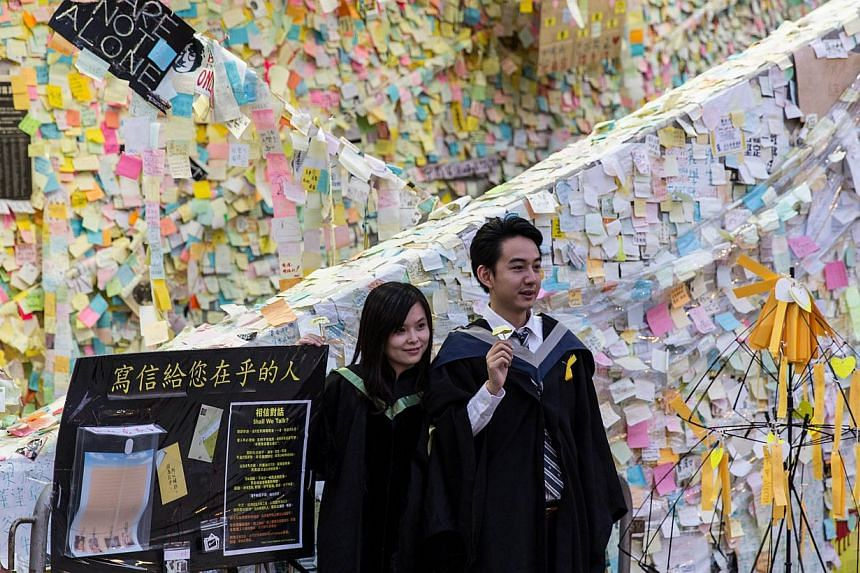 """Students wearing graduation gowns hold paper yellow umbrellas as they pose for a photo in front of the """"Lennon Wall"""" at a pro-democracy protest site in the Admiralty district of Hong Kong on Nov 24, 2014. -- PHOTO: AFP"""