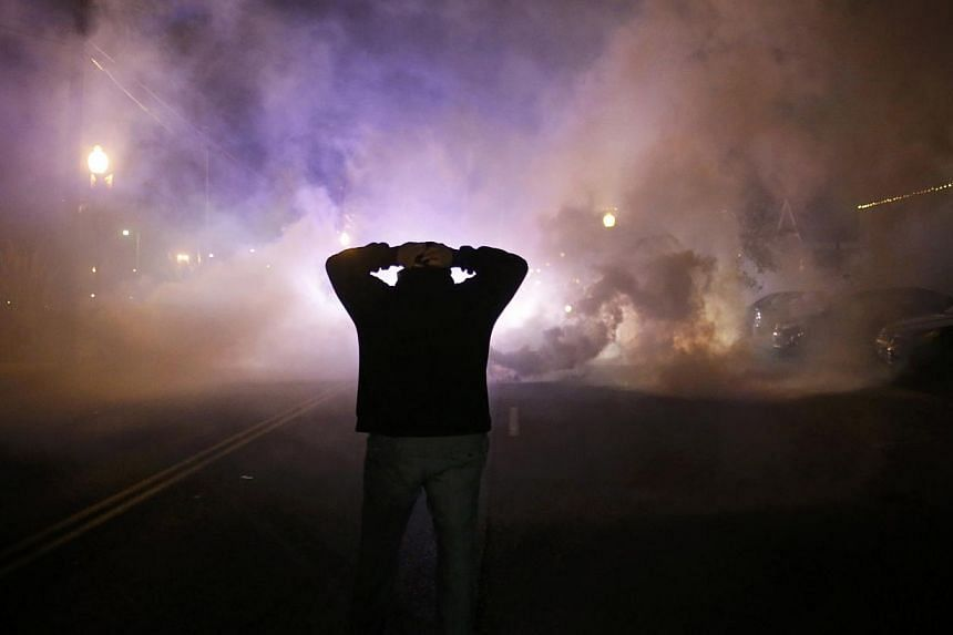 A protester stands with his hands on his head as a cloud of tear gas approaches after a grand jury returned no indictment in the shooting of Michael Brown in Ferguson, Missouri, on Nov 24, 2014. -- PHOTO: REUTERS