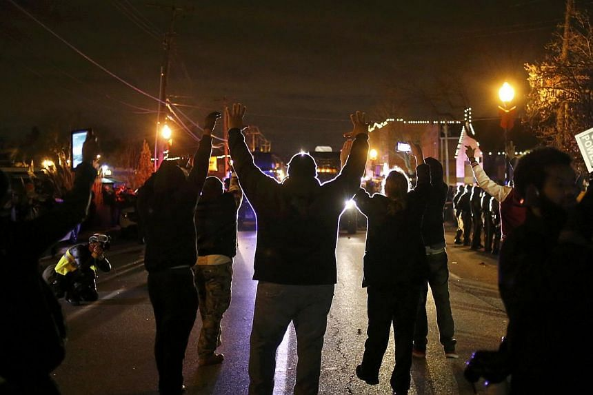 Protesters approach a police line with their hands up after a grand jury returned no indictment in the shooting of Michael Brown in Ferguson, Missouri, on Nov 24, 2014. -- PHOTO: REUTERS
