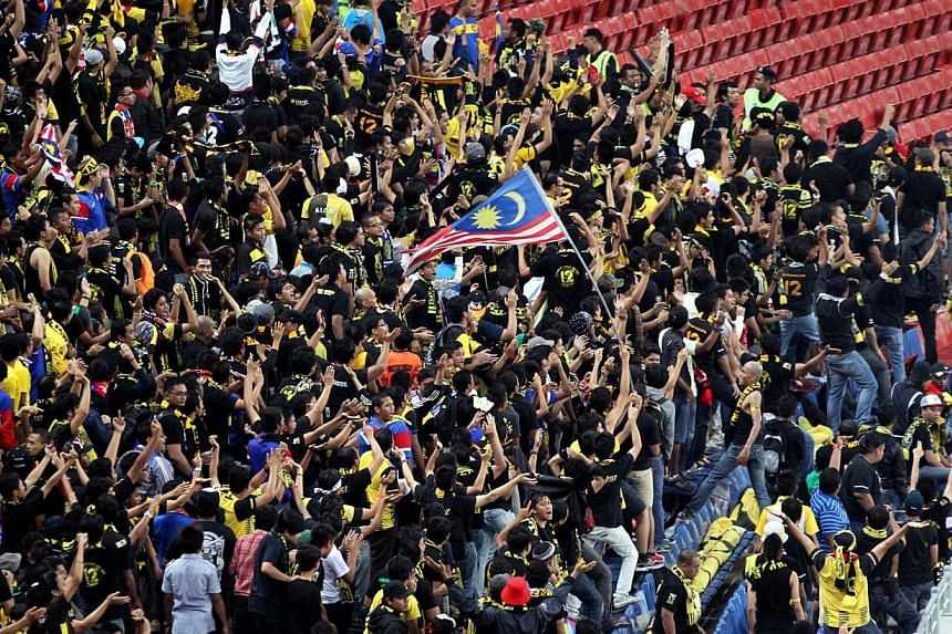 Malaysian football fans cheering during the Asean Football Federation (AFF) Suzuki Cup match between Malaysia and Laos on 28 Nov 2012. Malaysia's Youth and Sports Minister Khairy Jamaluddin has raised questions over the Singapore authorities' al