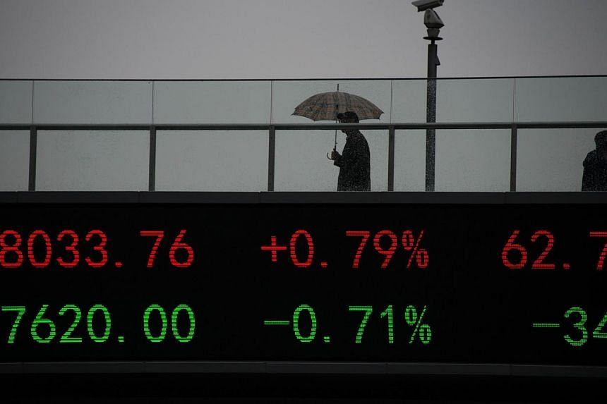 People wake on a bridge with a board showing the numbers of worlds stock exchange rates in the Lujiazui Financial District of Shanghai on Nov 25, 2014.Shanghai's stock index reached a multi-year high on Tuesday as investors remained optimistic