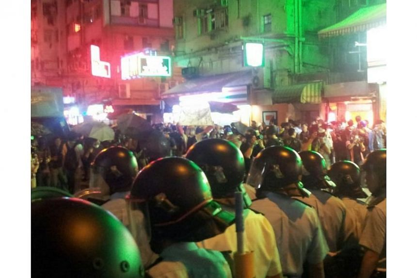 Hong Kong police in helmets in a stand-off with pro-democracy protesters at a site in Mong Kok -- ST PHOTO: PEARL LIU