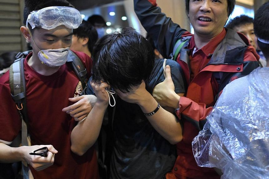 """A protesters is helped after being sprayed with what police described as """"tear spray"""" as officers attempted to clear demonstrators from a pro-democracy protest site in the Mong Kok district of Hong Kong on Nov 25, 2014. -- PHOTO: AFP"""