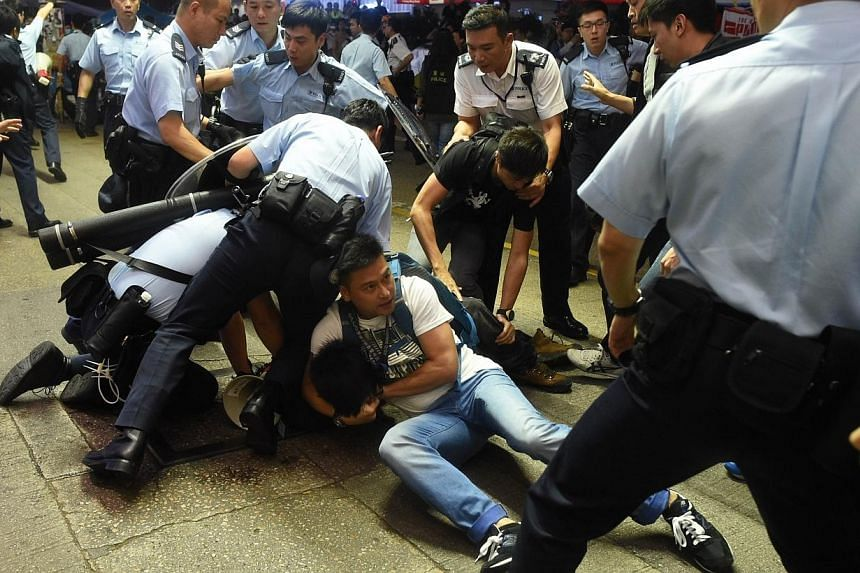 Police arrest a protester as they try to clear a road at a pro-democracy protest site in the Mong Kok district of Hong Kong on Nov 25, 2014. -- PHOTO: AFP