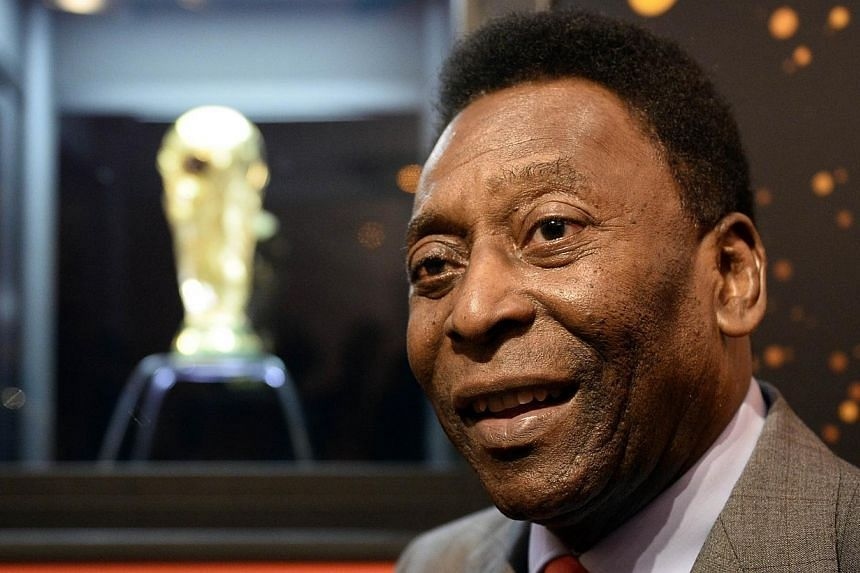 Brazilian football legend Pele answers journalist's questions next to the FIFA World Cup trophy during a press conference, on March 9, 2014 outside the Hotel de Ville in Paris.Brazilian football legend Pele was back in hospital Monday in Sao Pa