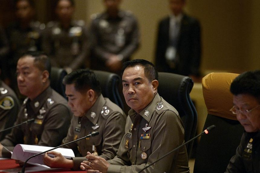 Thai national police chief Somyot Poompanmoung (centre) attends a press conference at the Royal Thai Police headquarters in Bangkok on Nov 25, 2014.Thai police said Tuesday they have charged a third high-ranking officer with lese majeste and al