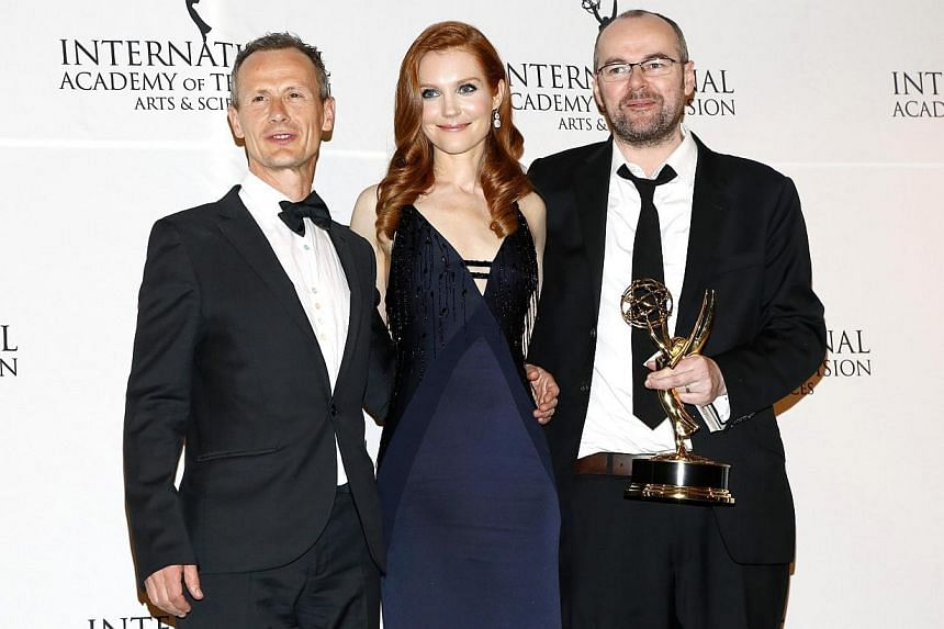 Director Marc Munden (left) and writer/creator and executive producer Dennis Kelly of British crime television series Utopia, backstage with their award for Drama Series, with actress Darby Stanchfield at the 42nd International Emmy Awards in New Yor
