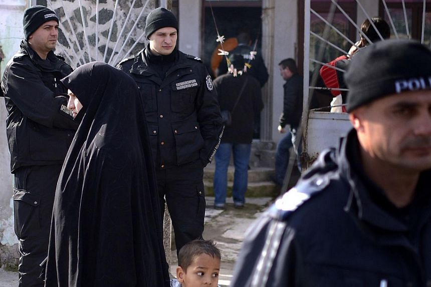 Policemen stand guard, during a search operation of a house in the Roma suburb in the city of Pazardjik, South West Bulgaria on Nov 25, 2014. Bulgarian authorities raided a mosque in the south of the country Tuesday as part of a probe into a loc