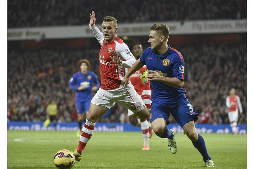 Manchester United's Luke Shaw (right) is challenged by Arsenal's Jack Wilshere during their English Premier League football match at the Emirates Stadium in London on Nov 22, 2014.-- PHOTO: REUTERS