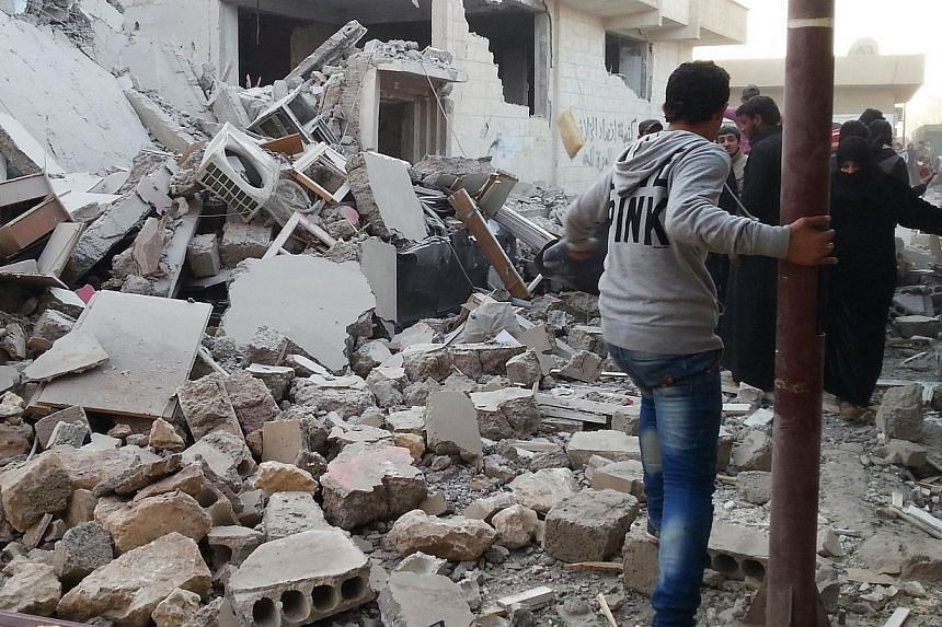 Syrian regime air raids on Raqa city, which the Islamic State in Iraq and Syria extremist group has proclaimed as its capital, killed at least 63 people, more than half of them civilians on Tuesday, a monitoring group said. -- PHOTO: AFP