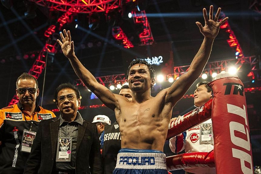 Manny Pacquiao of the Philippines (centre) celebrates his victory over Chris Algieri of the US (not pictured) after their world welterweight championship boxing bout at the Cotai Arena in Macau on Nov 23, 2014.Manny Pacquiao is open to ta