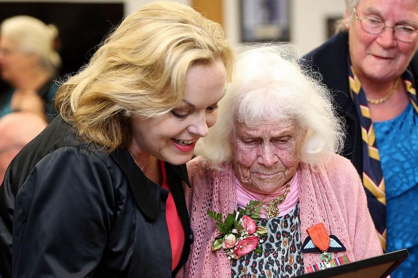 New Zealand's member of parliament Judith Collins (left) and Phyllis Latour Doyle look at the Knight of the national Order of the Legion of Honour award she received from French Ambassador to New Zealand Laurent Contini in Auckland on Nov 25, 2014.&n