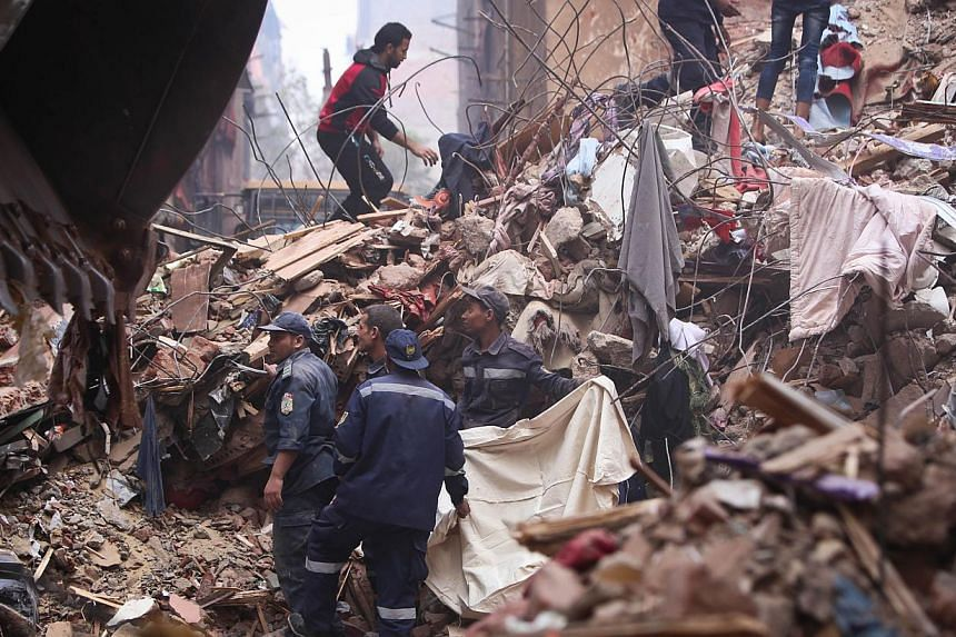 Egyptian rescue workers and residents search for survivors in the rubble of a collapsed building on Nov 25, 2014 in Cairo's northern district of Matariya. A building in Egypt's capital, where two floors had been added illegally, collapsed overnight,