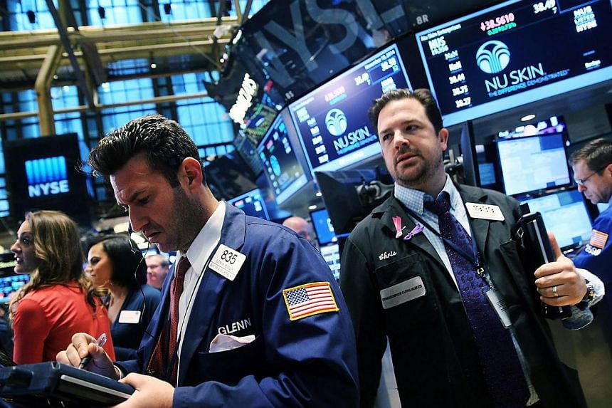 Traders work on the floor of the New York Stock Exchange (NYSE) in New York City on Nov 18, 2014. -- PHOTO: AFP