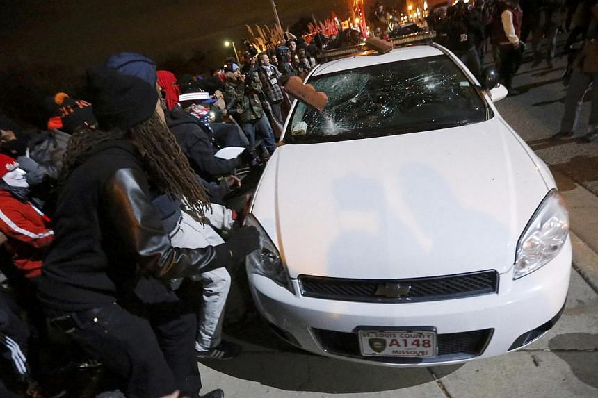 Protesters vandalise a car outside the Ferguson Police Department in Ferguson, Missouri, after a grand jury returned no indictment in the shooting of Michael Brown, on Nov 24, 2014. -- PHOTO: REUTERS