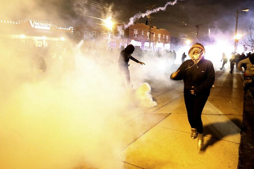 Protesters run from a cloud of tear gas after a grand jury returned no indictment in the shooting of Michael Brown in Ferguson, Missouri, on Nov 24, 2014. -- PHOTO: REUTERS