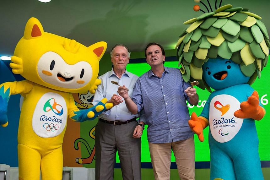 The president of the Brazilian Olympic Committee and head of the Rio 2016 Olympic Games Carlos Nuzman (left) and the mayor of Rio de Janeiro Eduardo Paes pose with the mascots for the Rio 2016 Olympic Games (yellow) and the Rio 2016 Paralympic Games,