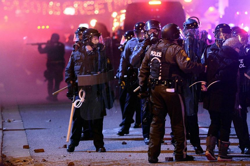 Police detain a protester during clashes over the decision in the shooting of 18-year-old Michael Brown in Ferguson, Missouri, on Nov 24, 2014. -- PHOTO: AFP