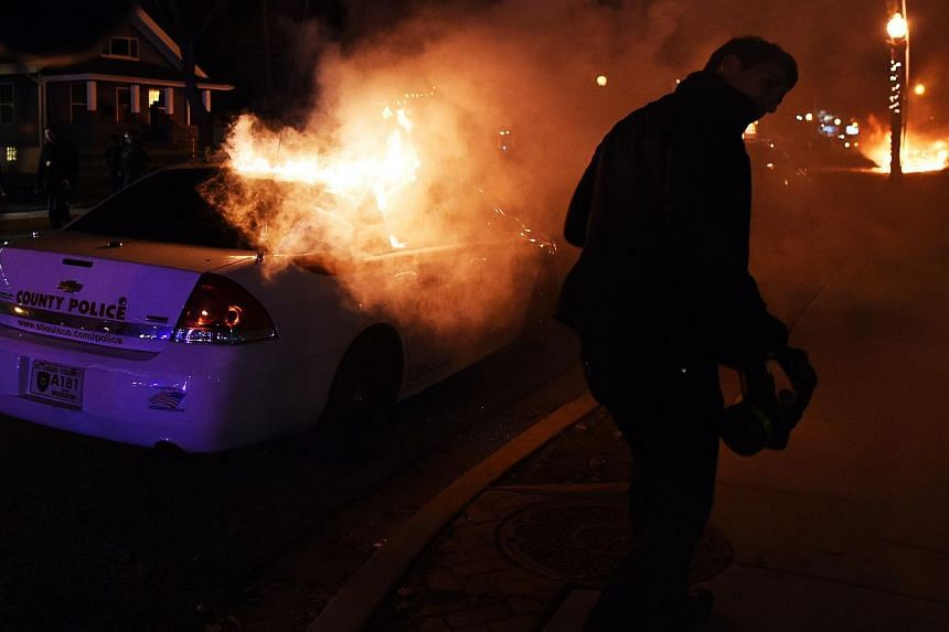 Protesters set police cars on fire during clashes following the grand jury decision in the death of 18-year-old Michael Brown in Ferguson, Missouri, on Nov 24, 2014. -- PHOTO: AFP