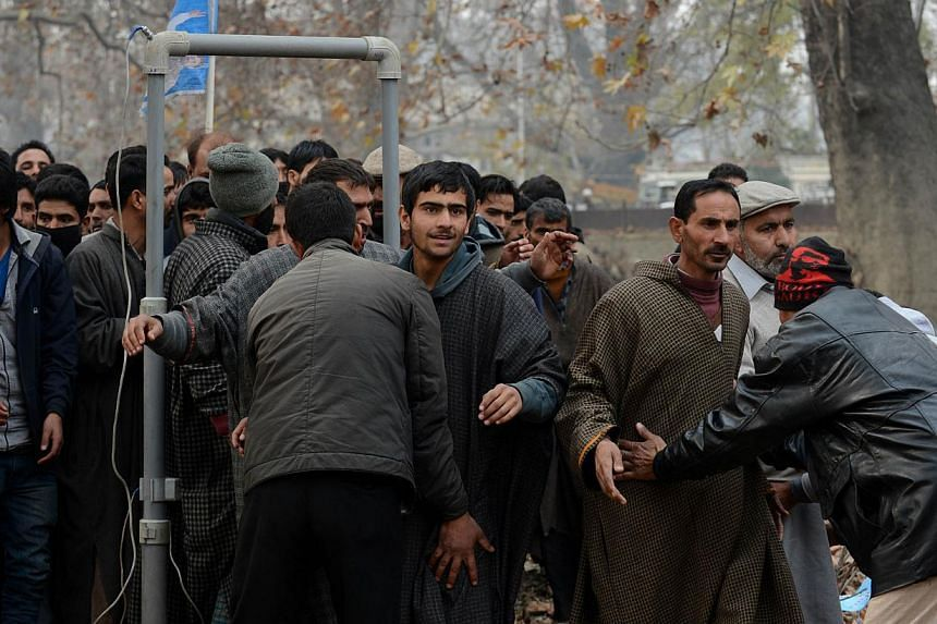 Plain-clothed Indian police personnel search Kashmiri supporters as they arrive for an election rally by the newly launched Peoples Republician Party (PRP) in Srinagar on Nov 24, 2014. -- PHOTO: AFP