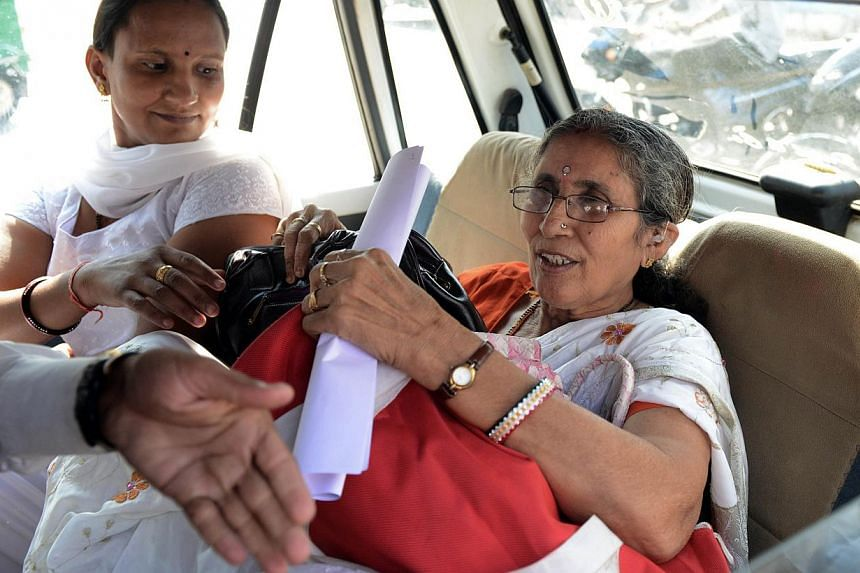 Indian Prime Minister Narendra Modi's wife, Ms Jashodaben (right), seated next to an unidentified woman, holding a copy of the Right To Information (RTI) application filed by her as she leaves the Deputy Superintendent of Police (DSP) office in Mehsa