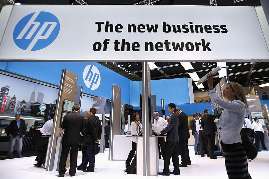 A visitor taking a photo  in front of an HP stand at the Mobile World Congress in Barcelona on Feb 27, 2014. Hewlett-Packard reported a 2.5 per cent drop in quarterly revenue, hurt by weak sales to enterprise customers. -- PHOTO: REUTERS