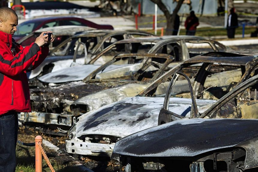 A man stops to take a photograph of burned and damaged cars following a night of rioting in Ferguson, Missouri, on Nov 25, 2014. -- PHOTO: REUTERS