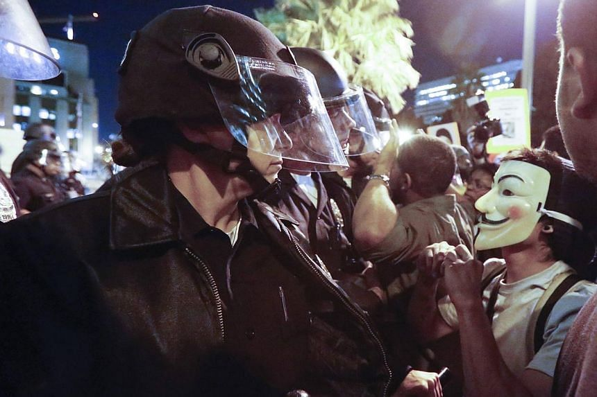 Protesters face off against a line of police during a demonstration outside LAPD headquarters in Los Angeles, California, following the Monday grand jury decision in the shooting of Michael Brown in Ferguson, Missouri, on Nov 25, 2014. -- PHOTO: REUT
