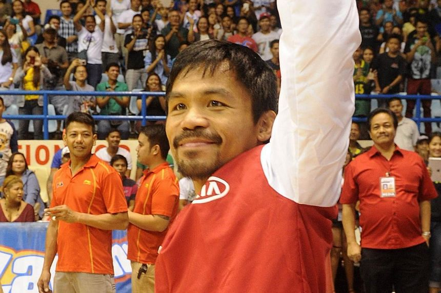 World boxing champion Manny Pacquiao waves to fans before taking part in a basketball game in Manila on Nov 26, 2014. Pacquiao resumed his Philippine pro basketball career on Wednesday with a crushing defeat that extended his team's losing streak to