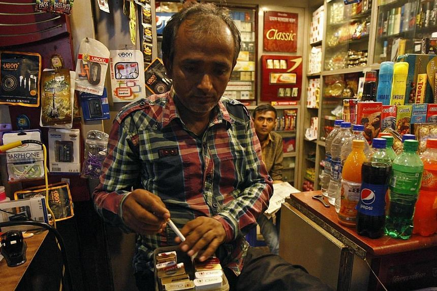 A shopkeeper takes out a cigarette from a box for a customer in Kolkata on Oct 15, 2014. Health campaigners on Wednesday welcomed India's plans to raise the age for tobacco purchases to 25 and ban unpackaged cigarettes, hailing them as a major s