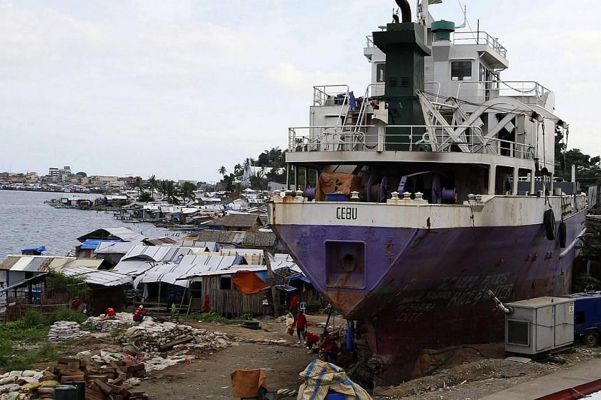 A ship which ran aground during last year's Typhoon Haiyan sits next to typhoon victims' temporary shelters in the central Philippines' Tacloban city on Nov 4, 2014. -- PHOTO: REUTERS