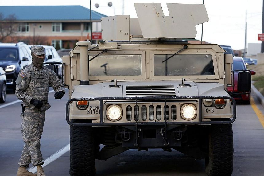 A National Guard walks by a Humvee in Clayton, Missouri on Nov 25, 2014 following a night of rioting in nearby Ferguson. -- PHOTO: REUTERS
