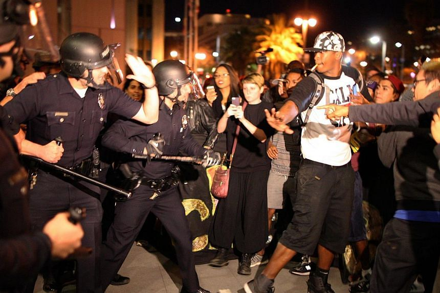 Protesters and police clash in front of LAPD Headquarters as people react to the grand jury decision not to indict a white police officer who had shot dead an unarmed black teenager in Ferguson, Missouri, in the early morning hours of Nov 25, 2014 in