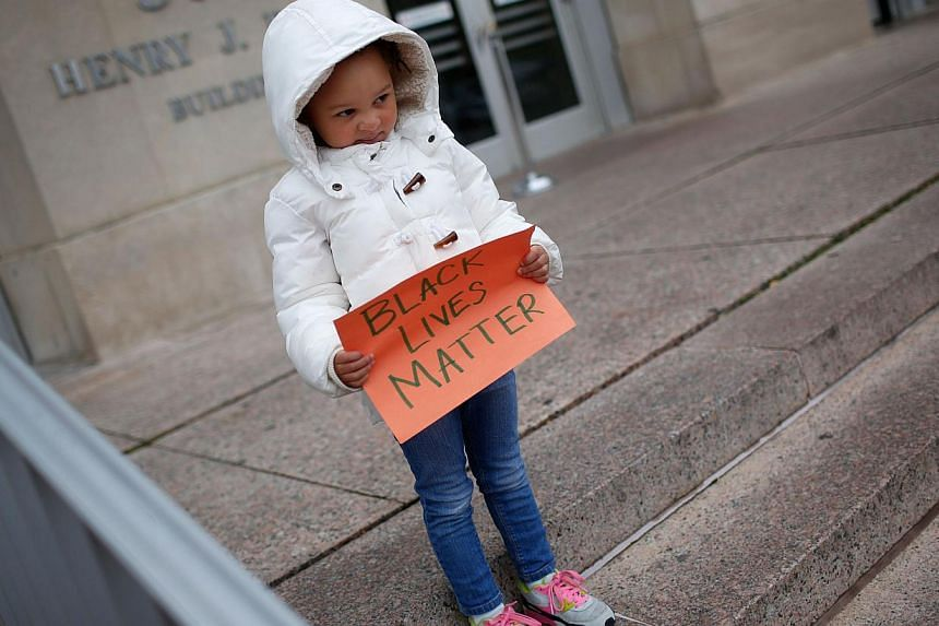 """4 year old Marley Hendrix Totten joins a group of protesters as they gather outside the headquarters of the Washington DC Metropolitan Police Department as part of a planned """"28 Hours for Mike Brown"""" protest in Washington, DC on Nov 25, 2014. -- PHOT"""