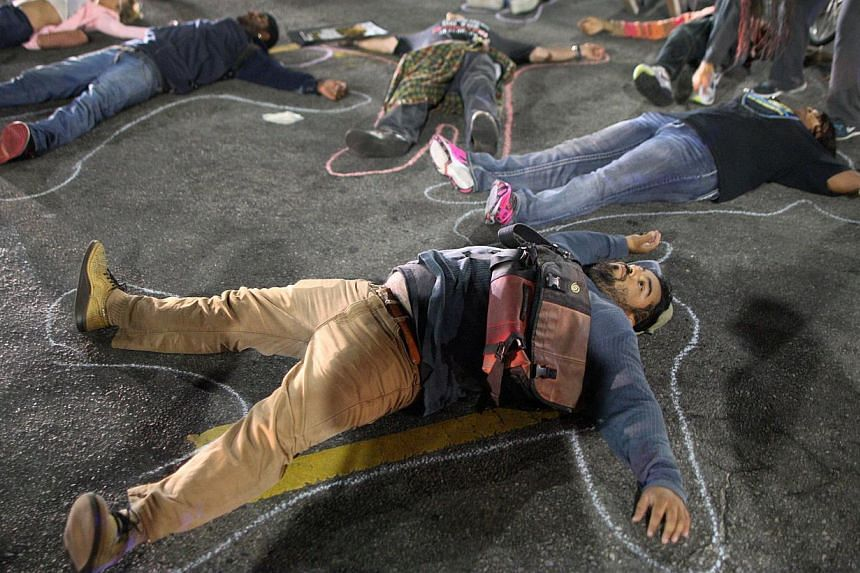 Protesters lie down in a major intersection to block traffic in reaction to the grand jury decision not to indict a white police officer who had shot dead an unarmed black teenager in Ferguson, Missouri in Los Angeles, California on Nov 24, 2014. --