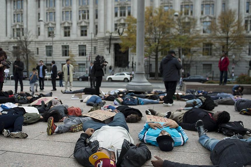 """Demonstrators with the group Black Youth Project 100 stage a """"lie-in"""" near the City Council offices in Washington, DC on Nov 25, 2014. The protesters are reacting to the Missouri grand jury's decision not to indict a white policeman, Darren Wilson, w"""