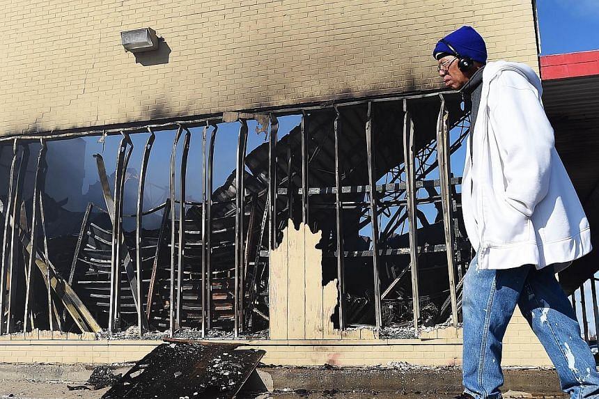 A man walks past a burnt out store, which was set ablaze following the grand jury decision in the fatal shooting of a 18-year-old black teenager Michael Brown, in Ferguson, Missouri on on Nov 25, 2014. -- PHOTO: AFP