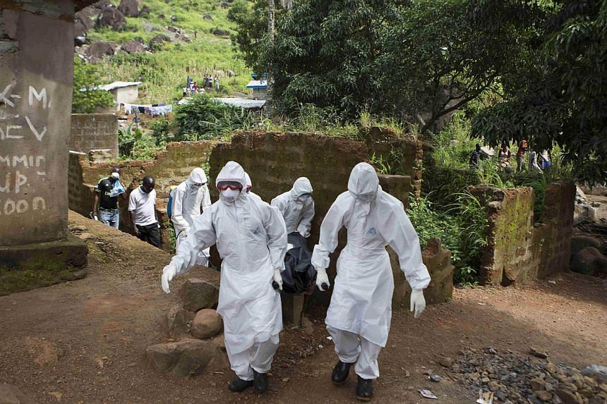 A burial team wearing protective clothing remove a body of a person suspected of having died of the Ebola virus, in Freetown Sept 28, 2014.Burial workers in Sierra Leone have dumped dead bodies in the street outside a hospital in protest at aut