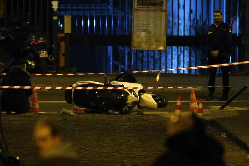 French police investigators gather evidence near a motor scooter in Paris' 15th arrondissement where two alleged robbers are reportedly entrenched in a hairdresser salon after attempting to rob a Cartier jewellery store on the Champs-Elysees on Nov 2