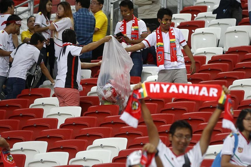 Myanmar fans clearing rubbish from the seats after the match between Singapore and Myanmar in the AFF Suzuki Cup at the National Stadium on Nov 26, 2014. -- ST PHOTO: KEVIN LIM