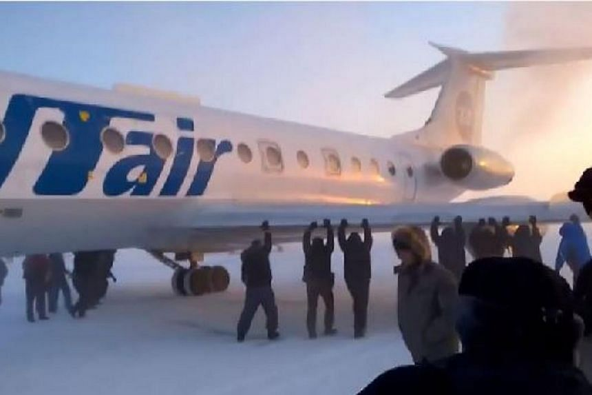 Passengers pushing the Tupolev plane on a snow-covered runway in Igarka, Russia, after its chassis froze due to temperatures of minus 52 degrees C. -- PHOTO: SCREENGRAB FROM YOUTUBE