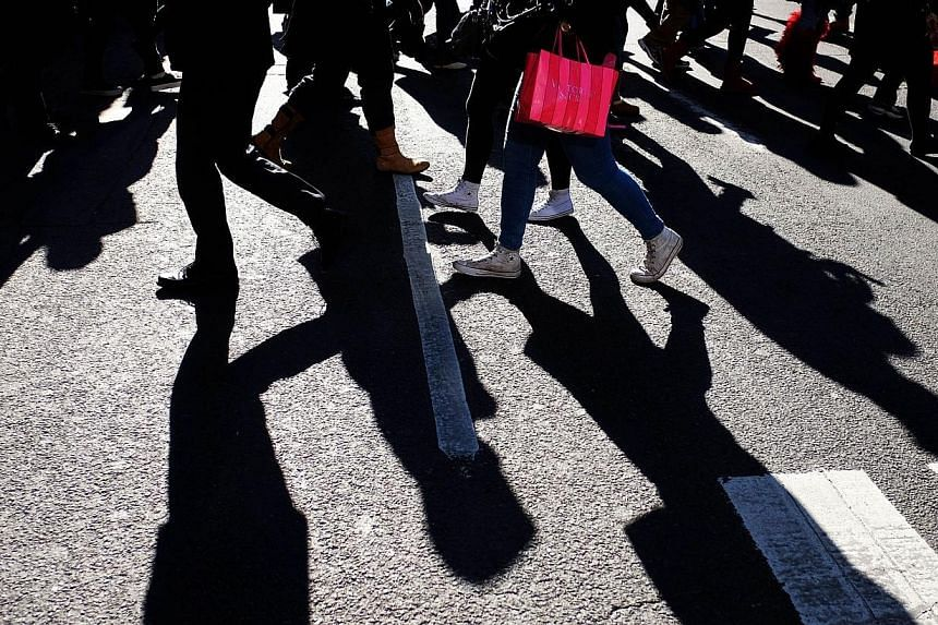 A woman walks with her shopping bag in New York this week. The US economy grew at a robust 3.9 per cent pace in the third quarter, stronger than previously estimated as business investment and consumer spending picked up, the Commerce Department said